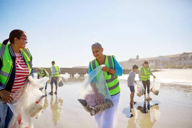 Groupe de personnes qui nettoient une plage