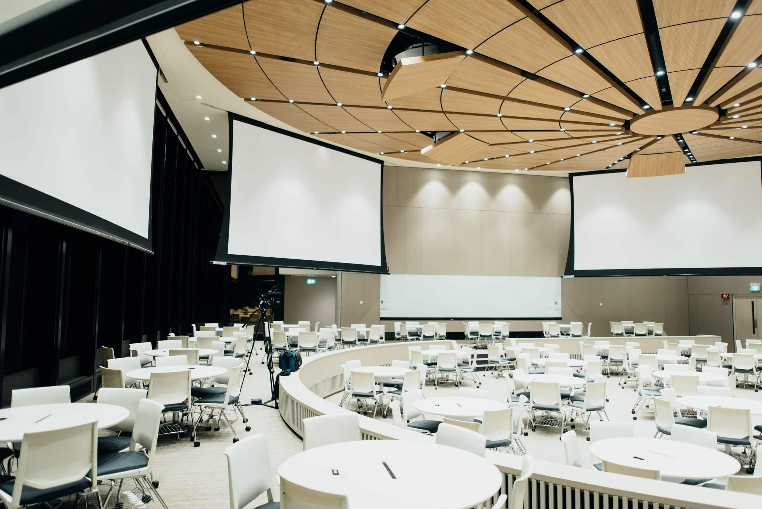 Grande salle avec des tables et des écrans pour un événement