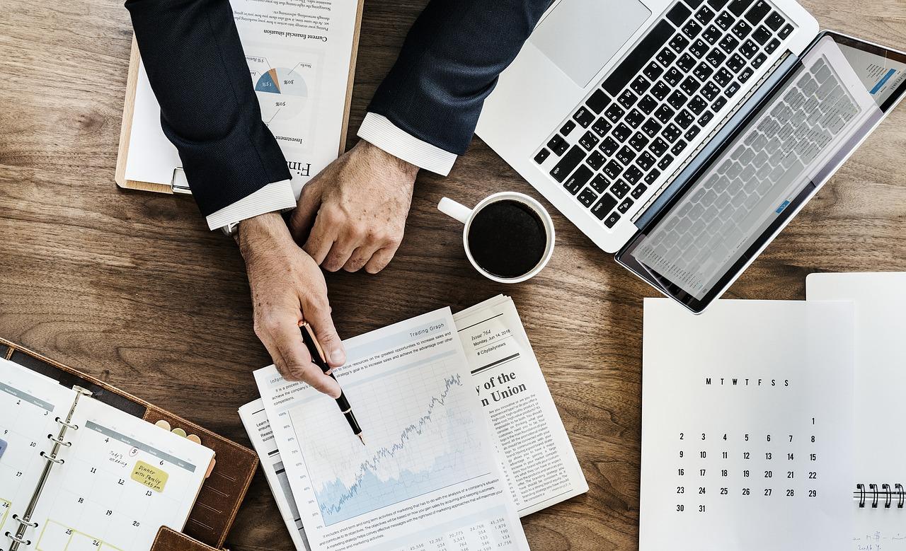 vue de haut sur un bureau avec ordinateur portable et documents et une personne qui montre un graphique