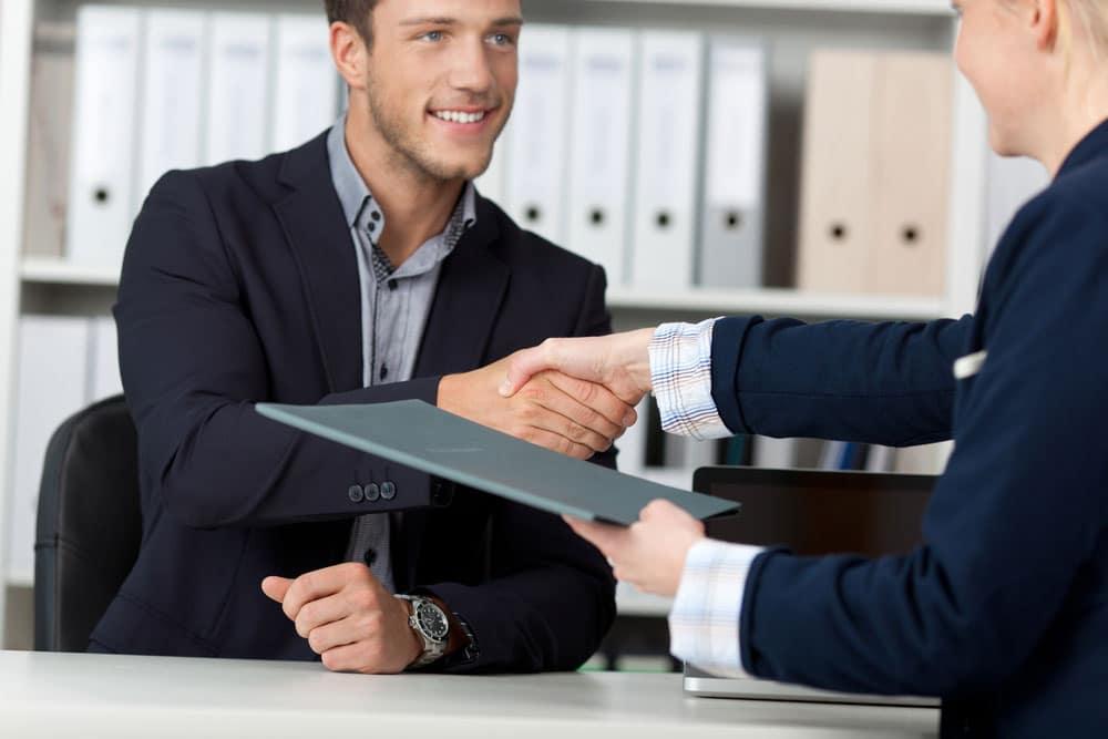 personnes se serrant la main au dessus d'un bureau l'une tenant un dossier