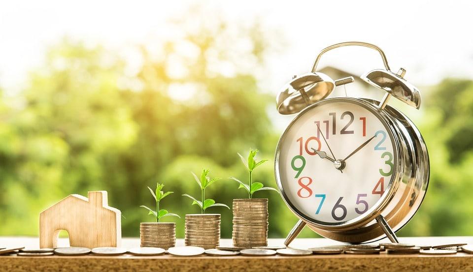 réveil pièces de monnaie empilées et maison en bois miniature