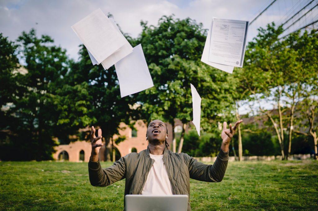 personne qui lance des documents au-dessus de sa tête